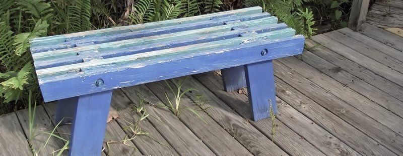 an old empty wooden peeling blue bench suffering from photobleaching