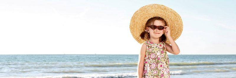 girl with sunglasses and giant floppy hat next to the beach